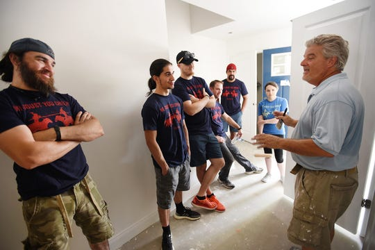 "Chris Warburton (R), Site Supervisor from Habitat For Humanity Bergen County, explains as Monica Garza (far rear, ""Queen Isabella"" and the ""Knights"" from Medieval Times, listen prior to beginning their work, as Medieval Times partners with Habitat For Humanity Bergen County to assist with their build project in Washington Township on 07/22/19. Habitat Bergen is building four 2-bedroom affordable homes. Two will be for military veterans and two will be for seniors."