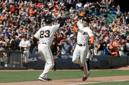 San Francisco Giants' Mike Yastrzemski, right, is congratulated by third base coach Ron Wotus (23) after hitting a solo home run against the New York Mets during the 12th inning of a baseball game in San Francisco, Sunday, July 21, 2019. (AP Photo/Jeff Chiu)