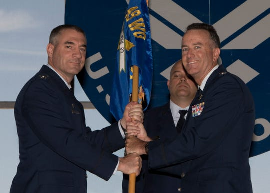 (From left to right) Col. Joseph Campo, 49th Wing commander, hands the 49th Operations Group flag to Col. Casey Tidgewell, 49th OG commander, during the Change of Command ceremony, July 12, on Holloman Air Force Base, N.M. Tidgewell returns to Holloman for a second tour as the 49th OG commander.