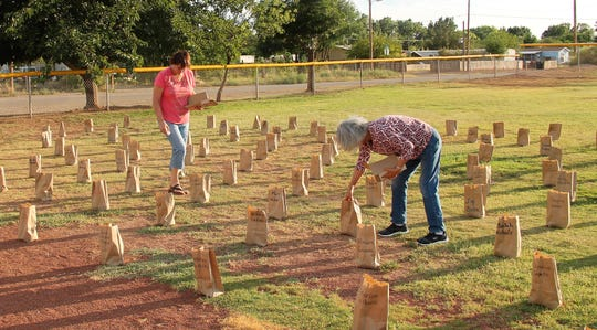 Andrea Toogood, left, and her mother Irene Kowatch, right, set up luminarias for Tularosa Basin Downwinders Consortium Candlelight Vigil, Saturday, July 20.