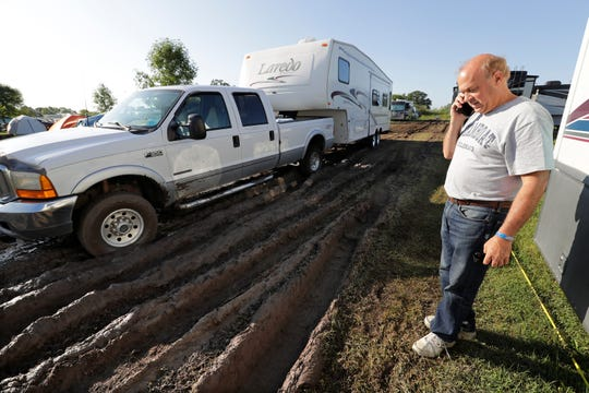 Steve McClintok of Windsor, Colo., calls a freind to help him tow his truck and trailor shortly after getting stuck in deep mud during EAA AirVenture Monday, July 22, 2019, at Wittman Regional Airport in Oshkosh, Wis.