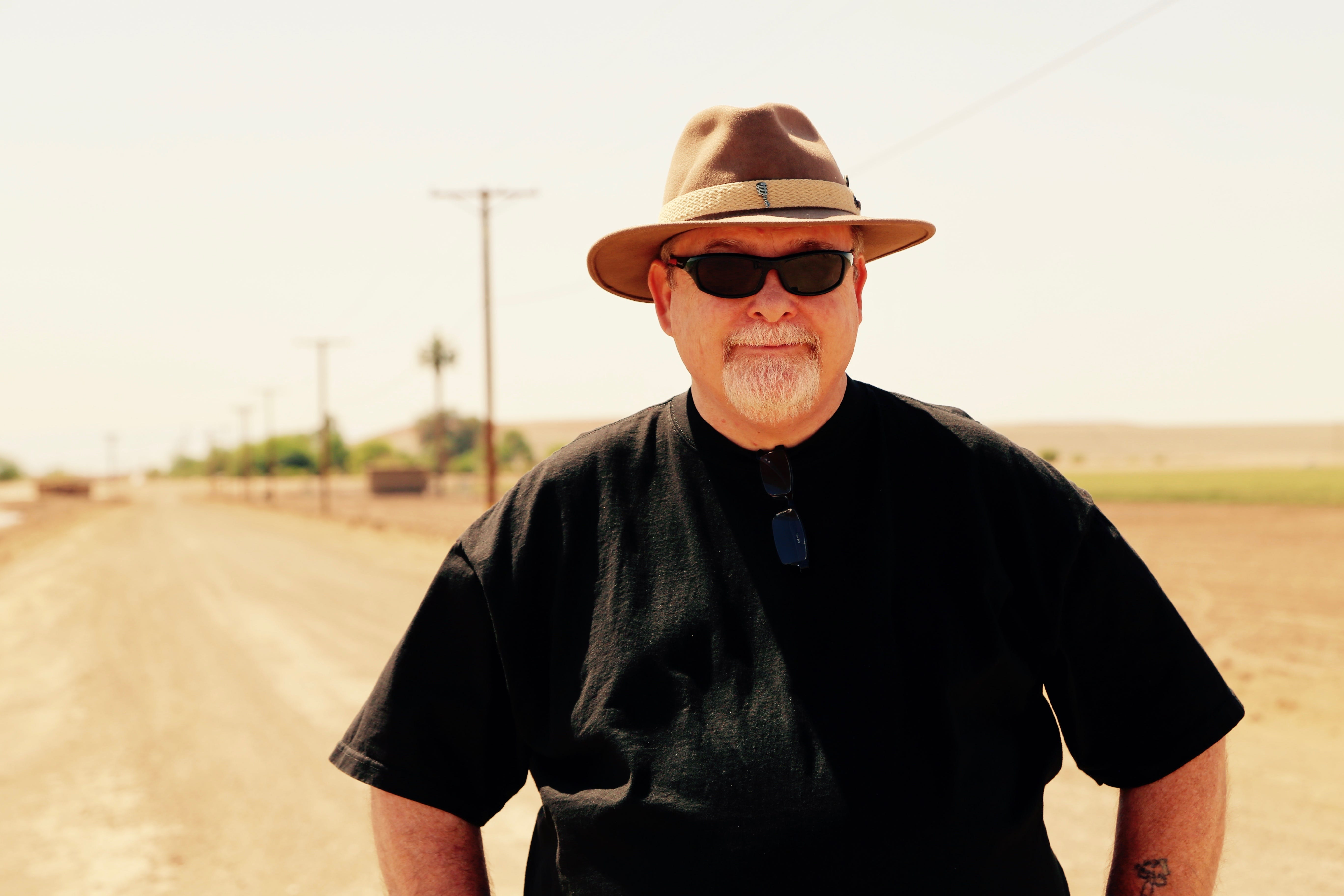 John Grasson stands at a dirt road intersection in Imperial, Calif., where he believes the lost ship of the desert may be buried.