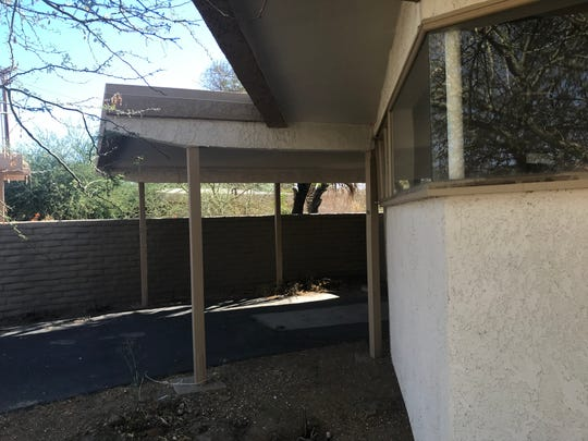 The pole in the window was a standard creation of mid-century architect Walter S. White who wanted his homes to drink in their surrounding views and natural sunlight. Over the years, the original wood exterior of the bungalows, built in 1957, has been covered over with stucco.