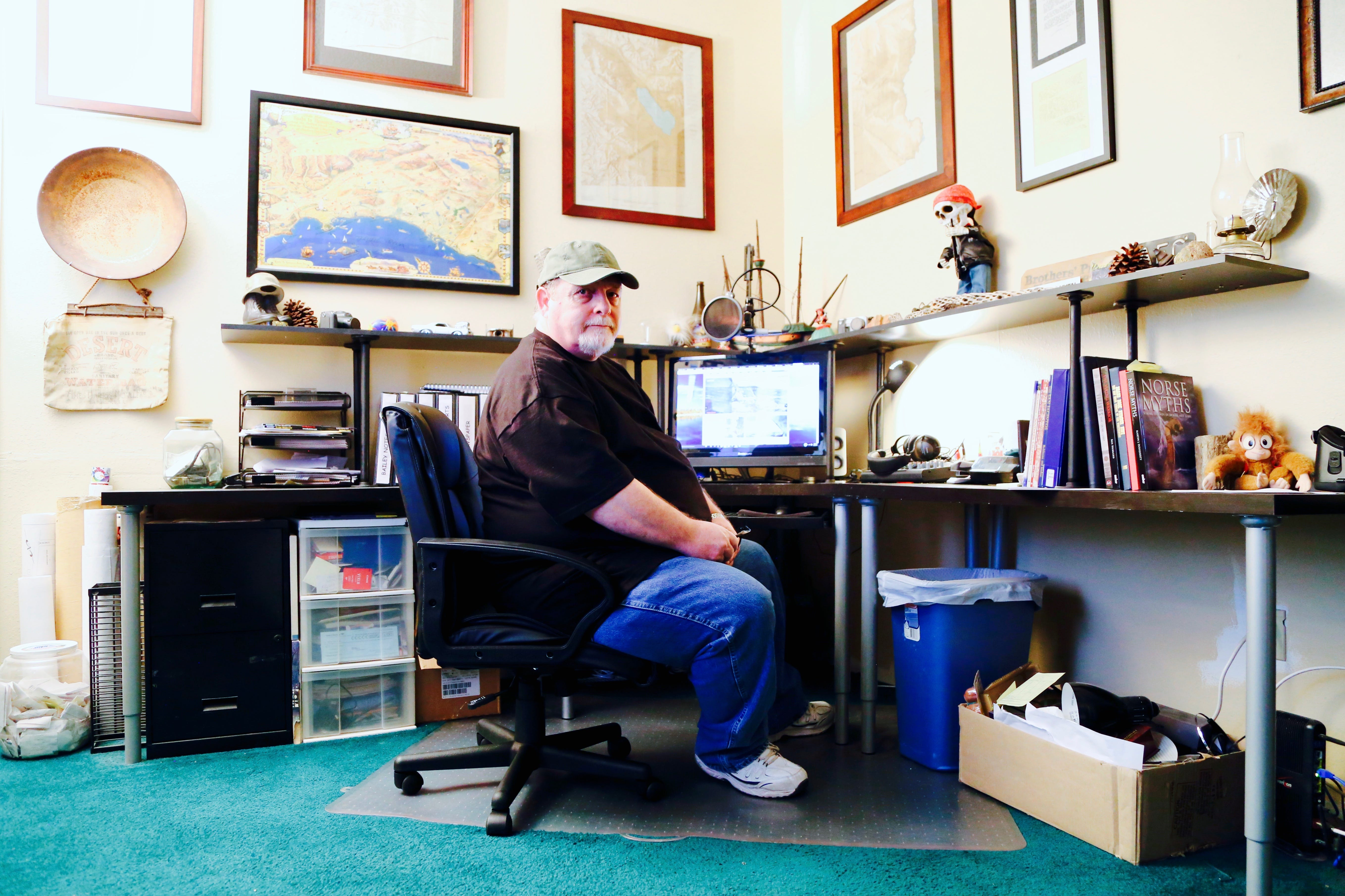 """John Grasson sits at his desk in his home in Banning, Calif., where he once published """"Dezert Magazine."""" Now, he searches for the lost ship of the desert."""