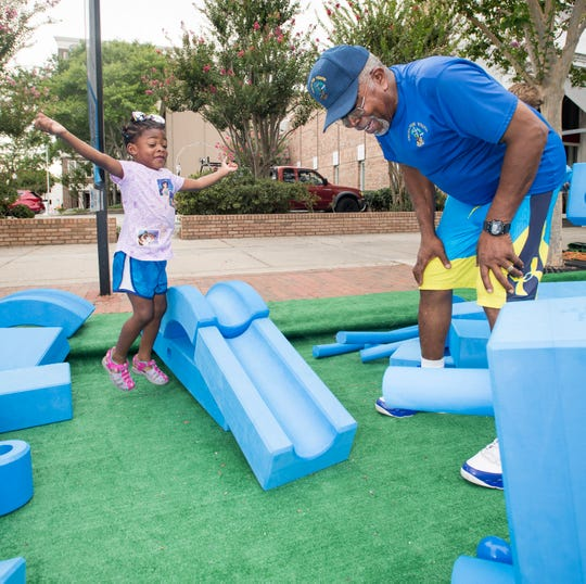 Truth For Youth executive director Rev. John H. Powell, right, smiles as Madison Jones, 4, jumps for joy after the ball successfully rolled downt the ramp they built with Imagination Playground Blue Blocks during Gallery Night on Palafox Street in downtown Pensacola on Friday, July 19, 2019. Powell was selected as Imagination Playground's 2019 Summer Block Champion for his use of the Blue Blocks to help spark fun and creative thinking in children.