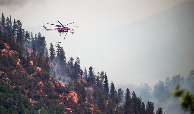A helicopter flies past areas of fire retardant that was dropped on the Museum Fire that still burns north of Flagstaff on July 22, 2019.