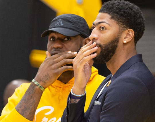 Los Angeles Lakers NBA basketball players, LeBron James, left, and Anthony Davis share a moment after Davis was introduced at a news conference at the UCLA Health Training Center in El Segundo, Calif., Saturday, July 13, 2019. (AP Photo/Damian Dovarganes)