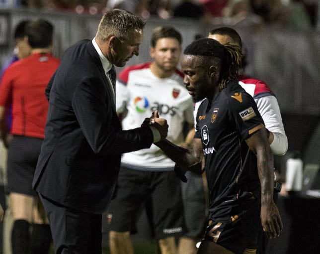 Phoenix Rising's manager Rick Schantz greets Mustapha Dumbuya (24) during the first half at Casino Arizona Field in Scottsdale July 19, 2019.