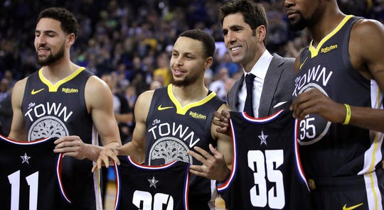 Golden State Warriors general manager Bob Myers, third from left, presents All-Star jerseys to Klay Thompson (11), Stephen Curry (30) and Kevin Durant (35) prior to an NBA basketball game against the Utah Jazz, Tuesday, Feb. 12, 2019, in Oakland, Calif. (AP Photo/Ben Margot)