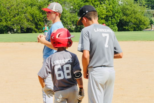 Connor Lawrence, right, coaches his younger brother, Cooper Lawrence, before his at-bat at Windsor's Summer Sandlot Camp.