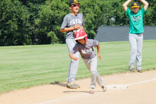 Connor Lawrence, left, coaches third base as his younger brother, Cooper Lawrence, attempts to score a run during Windsor's Summer Sandlot Camp.