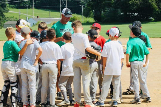 Red Lion baseball coach Kevin Lawrence discusses with the younger group of players his high-ace philosophy on the field at Windor's Summer Sandlot Camp.