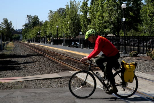 A cyclist rides past the railroad crossing at Mill St. SE and 12th St. SE in Salem on July 22, 2019.