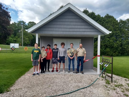 Celebrating the completion of the shed with a ribbon cutting are (pictured from left to right) Bryce Mathes, Connor Mueller, Joseph Trevino, Sean Thuemmler, Evan Thuemmler, Ben Hanson and Phil Hanson.