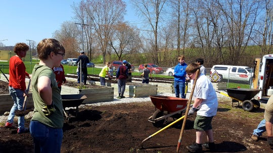 Members of Eagle Scout Ben Hanson's family and Boy Scout Troop 801 helped move dirt to the raised garden flower beds at Fresh Meals on Wheels.