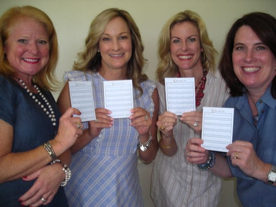 Demoiselle Deb moms plus one hold up Bunco cards at the Bunco Party: Rebecca Jackson, Demoiselle Ball Chief Mary Tipton, Ginger Lukacs, Tracy Prestwood.