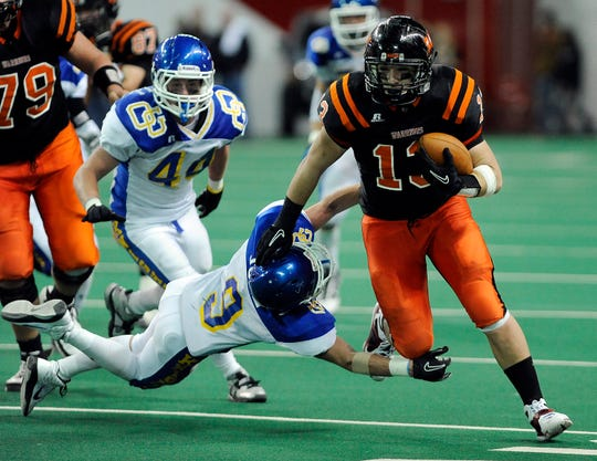 Washington's Brandon Mohr carries the ball as O'Gorman's Adam Juhl dives for his feet Saturday in the Class 11AA championship game at the DakotaDome. Defending champions, Washington beat O'Gorman 33-7 for the state title.(Elisha Page/Argus Leader)