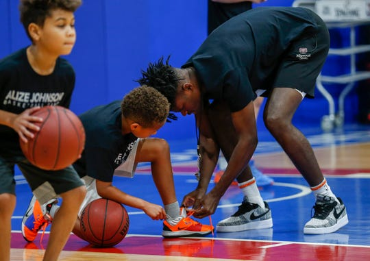 Indiana Pacers forward and Missouri State alumnus Alize Johnson helps a camper tie his shoe during his camp at The Basketball Movement in Nixa, Mo., on Monday, July 22, 2019.