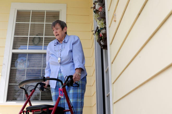 Linda Walker, a retired teacher and Southwood townhome owner, stands on her porch looking at the bubbles in the siding of her home. Over a hundred Southwood townhome owners are battling with a faulty siding issue with the company who first installed the product.