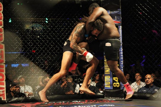 Austen Lane (red glove tape), a former Jacksonville Jaguars player, defeated Graceville's Cameron Graham in a heavyweight pro MMA fight during Combat Night Pro 14 at The Moon nightclub on July 20, 2019.
