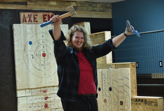"Jonathan Morgan, of Port St. Lucie, celebrates after winning a round of axe throwing, competing against his friends on Sunday, July 21, 2019, at Axe Em, an indoor axe throwing venue in Port St. Lucie. ""Great stress reliever,"" Morgan said. ""I always wanted to go to one of these places."""