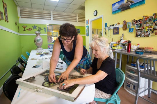 "Diane Concepción (left), co-owner of Pelican Central Mosaic Arts, and Maryanne Holbrook, of Fort Pierce, work on repurposing a stained glass piece passed down from Holbrook's father Friday, July 12, 2019, at The Mosaic Studio in Fort Pierce. ""At over 200 years old, it's really fragile,"" Holbrook said. ""Now at least I can put it up and be able to see it every day."""