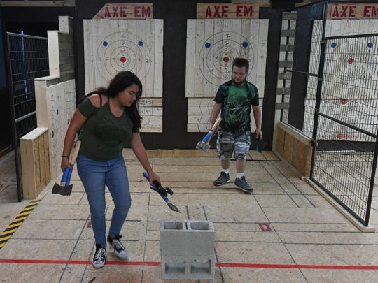 "Zadielys Soto, and Raymond Ahmad-Khan, both of Port St. Lucie, prepare to throw another round of axe throwing at Axe Em, a new indoor axe throwing venue in Port St Lucie. Games are played and scored similar to darts, with axes thrown against pine wood targets. ""It was very fun,"" Soto said. ""It's a very good stress reliever and a good workout to be here."""