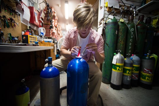 "Alex Barbieri, of Stuart, an employee at Deep Six Dive & Watersports in Stuart, helps prepare gear in the back room Monday, July 22, 2019, ahead of lobster mini-season July 24-25. ""I'm inspecting the tank, making sure it's safe to use for lobstering, diving,"" Barbieri said."