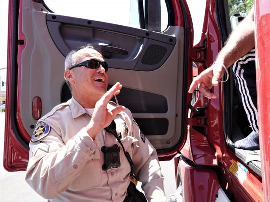 Ventura County Sheriff's Office Senior Deputy David Anaya banters while taking the license of a big rig driver he pulled over on Highway 118 in Moorpark during a commercial truck enforcement effort July 19. Truck traffic through the city is a major concern for residents.