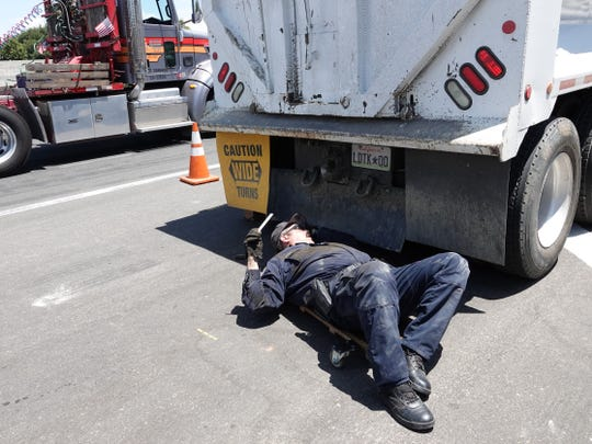 California Highway Patrol Officer Patrick O'Donnell rolls under a big rig during a roadside inspection on Highway 118 in Moorpark on July 19. A large volume of truck traffic through the city riles many residents.