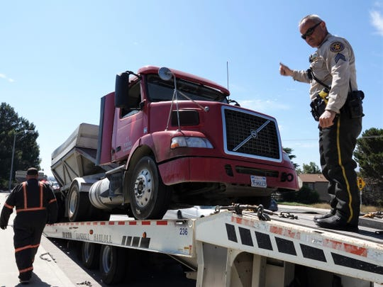 Ventura County Sheriff's Office Senior Deputy David Anaya directs a semi truck and trailer onto a tow truck after an inspection took the big rig out of service July 19 in Moorpark.