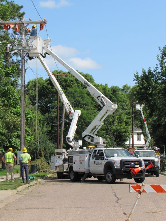 Crews from Waunakee Utilities work on power lines on Fourth Street South, near the corner of Chestnut Street, in Wisconsin Rapids Monday, July 22, 2019, following weekend storms that left widespread damage in the area.