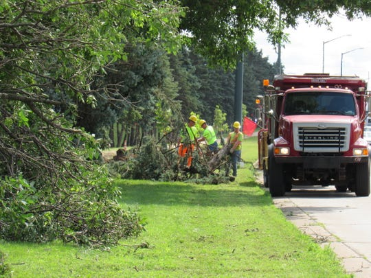 City street crews remove fallen trees along Riverview Expressway in Wisconsin Rapids Monday, July 22, 2019, following weekend storms that caused widespread damage in the area.