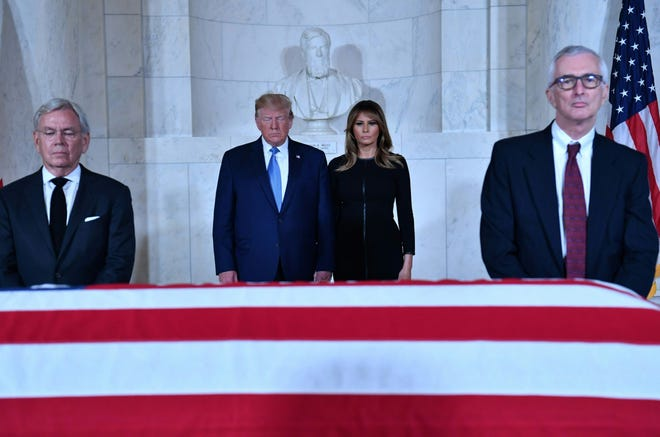 President Donald Trump and First Lady Melania Trump pay their respects before the flag-draped casket of late Supreme Court Justice John Paul Stevens in the Great Hall of the Supreme Court in Washington on Monday, July 22, 2019.