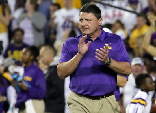 Ed Orgeron cheers on his players during warm-up drills before a 2018 game.