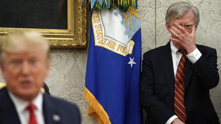 White House National Security Advisor John Bolton, right, listens to President Donald Trump in the Oval Office at the White House on July 18, 2019.