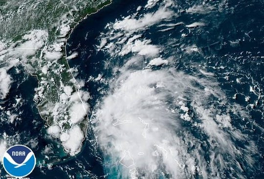 A satellite image shows a tropical depression spinning between the Bahamas and Florida.