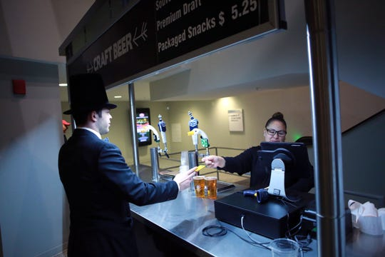 A Prudential Center attendee seen buying bear from a main concourse beer cart at the Newark arena.