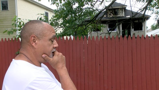 Keith Roberson reacts to finding out that a person was killed in a house fire in a home that is behind his backyard Tuesday morning, July 23, 2019.   The McBride Avenue home caught fire during the storms Monday evening.
