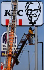 Jeff Fahntrapp with Acme Sign and Plastic welds the Kentucky Fried Chicken sign into place July 17. The new restaurant joins two others along South First Street in front of the new city of Abilene offices, including a new police department headquarters.