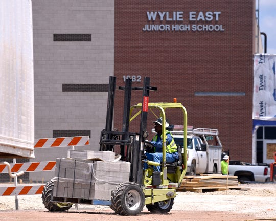 A worker carries a pallet of cinder blocks at the Wylie East Junior High School construction site Tuesday.
