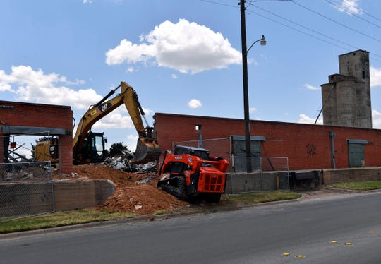 Heavy equipment clears debris during the renovation of the Cotton Exchange at 651 North First Street on Tuesday.