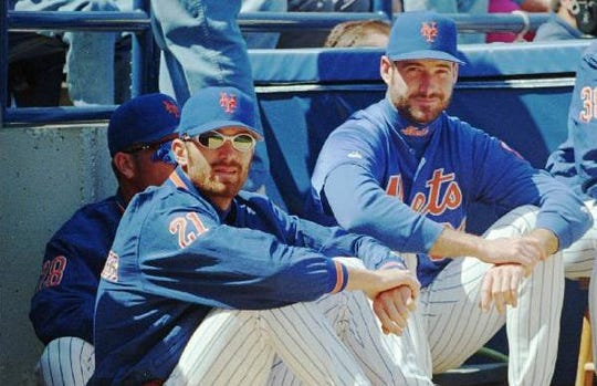 Sidelined with a strained tendon in his pitching elbow, New York Mets pitcher Bill Pulsipher (21) watches the game against the Detroit Tigers with teammate pitcher Paul Wilson Thurs., March 21, 1996 in Port St. Lucie, Florida.