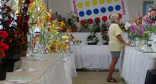 Deb Pigman serves as hostess for the Earth Wind and Flowers Garden Club during the flower show at the Crawford County Fair. This year's show had a board game theme with categories named after popular games such as Jenga, Connect Four and Candyland.