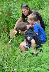 Lisa Bogard of the Crawford Park District helps Koltyn DeSimpelaere, 8, and Landon Beach, 7, look for pond life in the Lowe-Volk Park wetlands during a program Monday evening.
