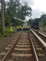 PATCO Hi-Speedline employees work Tuesday to restore electrical service to  a suburban portion of the Philadelphia-Lindenwold commuter line. They are replacing a damaged utility pole that caused a system between Cherry Hill and Lndenwold after a severe storm.