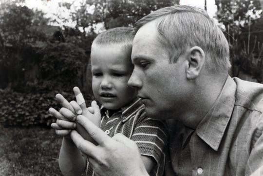 In this 1969 photo, Mark Armstrong, then 6, is comforted by his father Neil Armstrong after cutting his hand in a backyard accident.