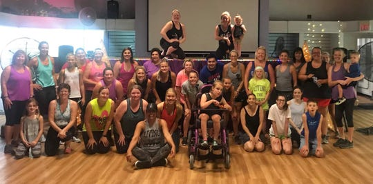 Hannah Owens sits with the people who came to the zumba fundraiser to raise money for a wheelchair accessible van for her family.