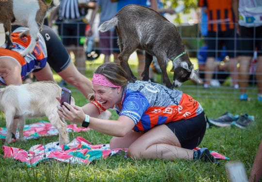 Molly Schebler of West Des Moines takes a selfie with a  goat on her back in the goat yoga pen at Howell's Greenhouse near Cumming during RAGBRAI on Tuesday, July 23, 2019.