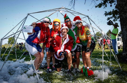 Cyclists from Team RWB pose for a photo in a makeshift snowglobe at the oasis at Howell's Greenhouse outside of Cumming during RAGBRAI on Tuesday, July 23, 2019.